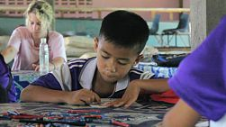 A cute Asian boy enjoys a coloring activity while learning English with a group of young adult overseas missionaries in Chiang Rai, Thailand.