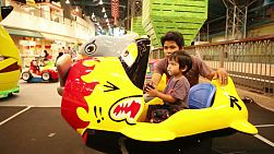A cute little 2 year old Asian boy enjoys an airplane ride at the mall in Bangkok, Thailand.
