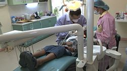 A left to right pan shot of a cute little 5 year old Asian boy gets his teeth cleaned at the dentist in Bangkok, Thailand.
