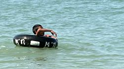 A cute Thai boy plays with an inner tube while floating in the ocean in Pattaya, Thailand.