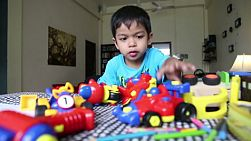 A cute little 4 year old Asian boy has fun playing with his tosy at home in Bangkok, Thailand.