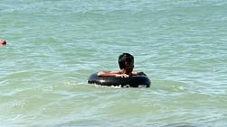 A cute Thai boy spinning in his inner tube while floating in the ocean in Pattaya, Thailand.