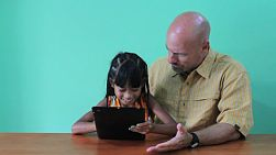 A cute little 7 year old girl shows her dad some new tricks on the digital tablet.