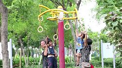 An Asian family has fun trying out some of the exercise rings at the local park in Bangkok, Thailand.