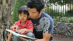 A loving father reads a book to his cute Asian son at the park.