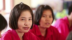 BURIRAM, THAILAND, SEPTEMBER 2013: A female Asian student recites a lesson with her classmates in school.