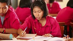 BURIRAM, THAILAND, SEPTEMBER 2013: A young female Asian student works on her school work in school.