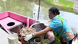 A Thai street food vendor in a canal boat is busy making a tasty spicy pork soup at the floating market in Bangkok, Thailand.