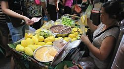 An Asian fruit seller lady sells fresh cut mango near the market in Bangkok, Thailand.