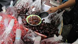 An Asian fruit seller lady sells fresh dried date fruit near the market in Bangkok, Thailand.