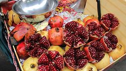 An Asian fruit seller lady sells fresh cut pomegranate near the market in Bangkok, Thailand.