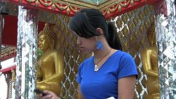 An attractive Thai woman sitting outside the temple in Bangkok, Thailand answers her cell phone.