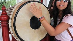 A cute Asian girl bangs on a large ceremonial drum at the temple in Bangkok, Thailand.