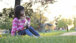A cute little eight year old Asian girl enjoys a nice cool slushy drink on a hot summer day at the park.