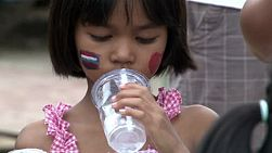 A cute little Thai girl drinking water in the slums of Bangkok, Thailand.