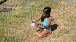 A cute little Asian girl has fun blowing up water balloons in the front yard in summer.