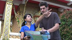 An attractive young Thai girl helps a lost foreign male tourist with directions in front of a Buddhist temple in Bangkok, Thailand.