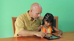 A cute little 7 year old Asian girl learns how to use a digital tablet with her father.