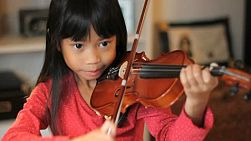 A pretty 6 year-old Asian girl diligently practices her violin in the living room.