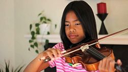 A pretty 9 year old Asian girl diligently practices her violin in the living room.