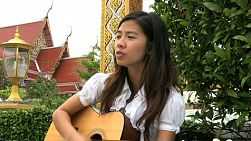 A young Thai female university student sings Christian worship songs on her guitar in Bangkok, Thailand.