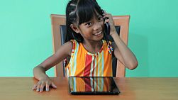 A cute little seven year old Asian girl talks on a smart phone while playing on her digital tablet.