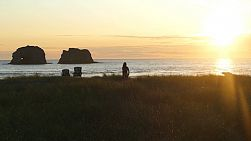A cute 13 year old Asian teenage girl enjoys watching a stunning summer sunset at Rockaway Beach on the Oregon Coast.