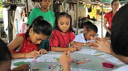 A group of cute Asian kids have fun coloring during an English lesson in the slums of Bangkok, Thailand.
