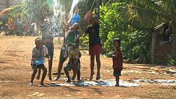 Thai children play with water, spraying each other to cool down during Songkhran in the middle of the hot season in the slums of Bangkok, Thailand.