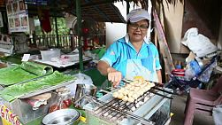 A Thai lady cooks grilled pork balls on skewers at the market in Bangkok, Thailand.