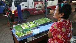 A Thai food vendor waits patiently for customers to come and buy her delicious food on the streets of Bangkok, Thailand.