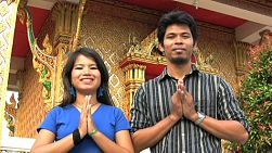 "An attractive Thai man and woman demonstrate the typical Thai ""wai"" greeting outside a Buddhist temple in Bangkok, Thailand."