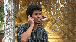 A Thai man sitting outside the temple in Bangkok talking on his cell phone to his friend.