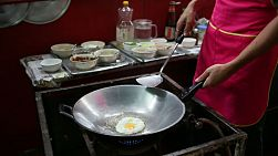 "A Thai man makes ""khai daow"", or a fried egg in a wok at the market in Bangkok, Thailand."