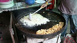 "An Asian man makes ""hoi tawd"", or fried mussels at the market in Bangkok, Thailand."