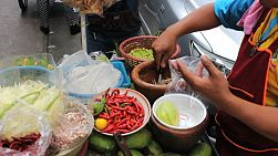 A Thai street vendor prepare fresh green spicy papaya salad near the market in Bangkok, Thailand.