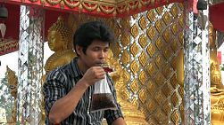 "An attractive Thai man sips on a refreshing cola drink in a bag with ice, ""Thai style"", in front of the temple."