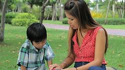 A pretty Thai mother patiently teacher her son to read while spending time together at the park in Bangkok, Thailand.