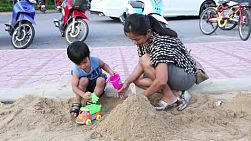 An Asian mother and her cute little boy enjoy spending time together playing in the sand box at the local park in Bangkok, Thailand.