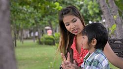 Young Asian mother and her son, sitting in a park, talking and counting together. Dolly tracking movement.