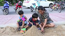 A pretty Asian mother plays with her two sons in the sand box at the local playground in Bangkok, Thailand.