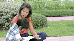 Young Asian mother helping teach her son to read and spending time together.