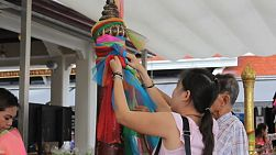 Thai people spend time praying and making merit at the local Buddhist temple in Bangkok, Thailand.
