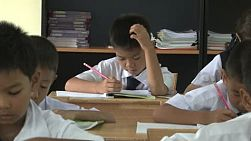 A group of Thai school boys are busy doing their school work in class in Chiang Mai, Thailand.