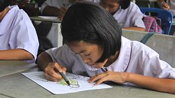 A cute female Asian school girl diligently colors her coloring sheet during an English class in Ratchaburi, Thailand.