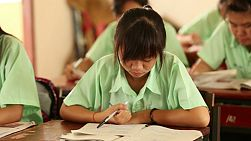 A young Thai female student studying in school in rural Thailand.