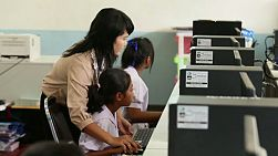 BURIRAM, THAILAND, SEPTEMBER 2013: A Thai teacher helps her students in the computer lab at school in Buriram, Thailand.