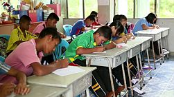BURIRAM, THAILAND, SEPTEMBER 2013:  A group of Asian students take a test in the classroom in Buriram, Thailand.