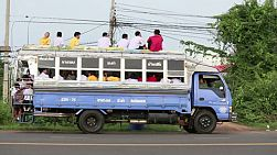 A group of Asian students take the bus home from school in Buriram, Thailand.