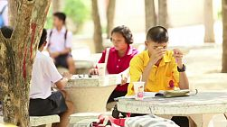 A group of Asian students work on some school work outside during their lunch break in Buriram, Thailand.